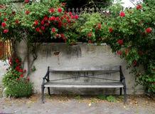 Ξεπερασμένες στάσεις πάγκων πάρκων μπροστά από έναν τοίχο πετρών με την αναρρίχηση των κόκκινων τριαντάφυλλων στοκ εικόνες