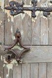 Ξεπερασμένη μεσαιωνική πόρτα με τη σκουριασμένες άρθρωση και τη λαβή Στοκ Φωτογραφία