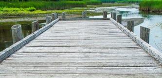 Ξεπερασμένη ξύλινη αποβάθρα που αγνοεί το ρηχούς ποταμό και την ελώδη περιοχή Στοκ Φωτογραφίες