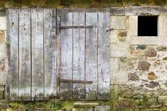 Ξεπερασμένη παλαιά πόρτα σιταποθηκών και πέτρινος τοίχος Στοκ Εικόνες
