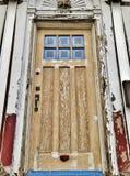 Ξεπερασμένη ραγισμένη μπροστινή πόρτα του παλαιού σπιτιού κάτω από την κατασκευή που χτίζει και που επισκευάζει το νέο σπίτι στοκ φωτογραφίες με δικαίωμα ελεύθερης χρήσης
