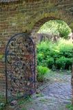 Ξεπερασμένοι τουβλότοιχοι και πύλη που οδηγούν στο θερινό κήπο Στοκ εικόνα με δικαίωμα ελεύθερης χρήσης