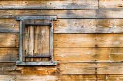Ξεπερασμένος ξύλινος τοίχος με το κλείνω με παντζούρια παράθυρο στην αποικιακή σιταποθήκη Στοκ Φωτογραφία