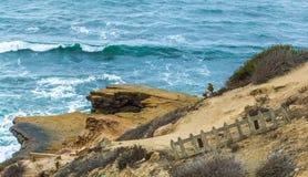 Ξεπερασμένος ξύλινος φράκτης στύλων σε έναν απότομο βράχο που αγνοεί το Ειρηνικό Ωκεανό Στοκ Εικόνα
