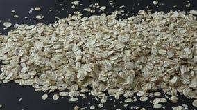 Ξεράνετε κυλημένο oatmeal που απομονώνεται στο μαύρο υπόβαθρο απόθεμα βίντεο