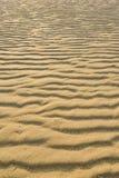 Ξεράνετε την κυματισμένη χρυσή άμμο, ιδανική για τα υπόβαθρα Στοκ Φωτογραφία