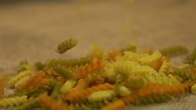 Ξεράνετε τη χρωματισμένη έκχυση ζυμαρικών στον γκρίζο σάκο, διαφήμιση της υγιούς παραγωγής προϊόντων φιλμ μικρού μήκους