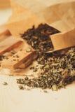 Ξεράνετε το τσάι φύλλων στο ξύλινο κύπελλο στο ξύλινο υπόβαθρο, ξηρό πράσινο τσάι φύλλων με το βιβλίο σημειώσεων στο ξύλινο υπόβα Στοκ Φωτογραφίες