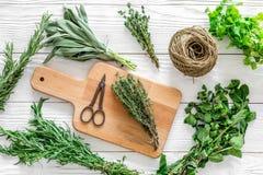 Ξεραίνοντας φρέσκα χορτάρια και greenary για τα τρόφιμα καρυκευμάτων στο άσπρο ξύλινο κουζινών γραφείων σχέδιο άποψης υποβάθρου τ Στοκ Εικόνα