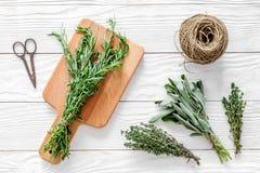 Ξεραίνοντας φρέσκες χορτάρια και πρασινάδα για τα τρόφιμα καρυκευμάτων στην άσπρη ξύλινη τοπ άποψη υποβάθρου γραφείων κουζινών Στοκ φωτογραφία με δικαίωμα ελεύθερης χρήσης