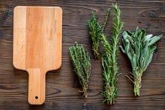 Ξεραίνοντας φρέσκες χορτάρια και πρασινάδα για τα τρόφιμα καρυκευμάτων στο ξύλινο κουζινών γραφείων διάστημα άποψης υποβάθρου τοπ Στοκ Εικόνες
