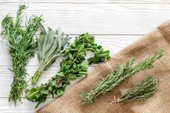 Ξεραίνοντας φρέσκες χορτάρια και πρασινάδα για τα τρόφιμα καρυκευμάτων στην άσπρη ξύλινη τοπ άποψη υποβάθρου γραφείων κουζινών Στοκ Εικόνες