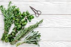 Ξεραίνοντας φρέσκες χορτάρια και πρασινάδα για τα τρόφιμα καρυκευμάτων στο άσπρο ξύλινο κουζινών γραφείων διάστημα άποψης υποβάθρ Στοκ εικόνα με δικαίωμα ελεύθερης χρήσης