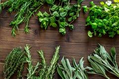 Ξεραίνοντας φρέσκες χορτάρια και πρασινάδα για τα τρόφιμα καρυκευμάτων στην ξύλινη τοπ άποψη υποβάθρου γραφείων κουζινών Στοκ εικόνες με δικαίωμα ελεύθερης χρήσης