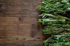 Ξεραίνοντας φρέσκες χορτάρια και πρασινάδα για τα τρόφιμα καρυκευμάτων στο ξύλινο κουζινών γραφείων διάστημα άποψης υποβάθρου τοπ Στοκ εικόνες με δικαίωμα ελεύθερης χρήσης