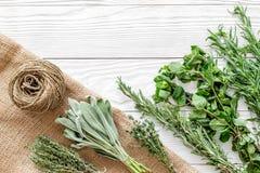 Ξεραίνοντας φρέσκες χορτάρια και πρασινάδα για τα τρόφιμα καρυκευμάτων στο άσπρο ξύλινο κουζινών γραφείων διάστημα άποψης υποβάθρ Στοκ φωτογραφία με δικαίωμα ελεύθερης χρήσης
