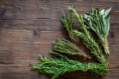 Ξεραίνοντας φρέσκες χορτάρια και πρασινάδα για τα τρόφιμα καρυκευμάτων στο ξύλινο κουζινών γραφείων διάστημα άποψης υποβάθρου τοπ Στοκ Εικόνα