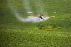 Ξεσκονόπανο συγκομιδών που ψεκάζει έναν αγροτικό τομέα στοκ φωτογραφίες