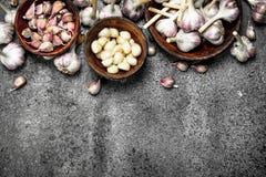 Ξεφλουδισμένες φέτες του φρέσκου σκόρδου στα κύπελλα Στοκ Εικόνες
