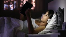 Ξεφύλλισμα εφήβων και μέσα προσοχής με μια ταμπλέτα και τα ακουστικά φιλμ μικρού μήκους
