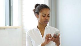 Ξεφύλλισμα Smartphone, μαύρη γυναίκα αποστολής κειμενικών μηνυμάτων Στοκ εικόνα με δικαίωμα ελεύθερης χρήσης