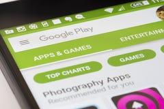 Ξεφύλλισμα του καταστήματος παιχνιδιού Google στο αρρενωπό smartphone Στοκ Φωτογραφία