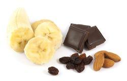 Ξεφλουδισμένη τεμαχισμένη μπανάνα με τη σοκολάτα, τα αμύγδαλα και τις σταφίδες Στοκ εικόνες με δικαίωμα ελεύθερης χρήσης