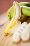 Ξεφλουδισμένη ώριμη μπανάνα στην πράσινη ακατέργαστη μπανάνα στοκ εικόνες