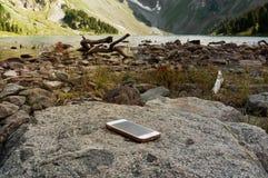 Ξεχασμένο άσπρο smartphone σε έναν βράχο στοκ εικόνες