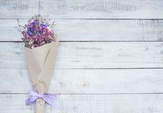 Ξηρά ανθοδέσμη λουλουδιών στο καφετί έγγραφο για το ξύλινο υπόβαθρο Στοκ Εικόνες