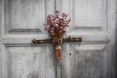 Ξηρά ανθοδέσμη σε μια παλαιά πόρτα Στοκ Φωτογραφίες