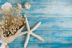 Ξηρά ανθοδέσμη, κοχύλια θάλασσας και αστερίας σε ένα μπλε αγροτικό υπόβαθρο Στοκ Εικόνα