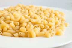 Ξηρά ζυμαρικά μακαρονιών στο άσπρο πιάτο Στοκ φωτογραφίες με δικαίωμα ελεύθερης χρήσης