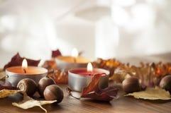 Ξηρά ζωηρόχρωμα φύλλα φθινοπώρου και βελανίδια της βόρειας κόκκινης βαλανιδιάς στον ξύλινο πίνακα με τρία καίγοντας κεριά Στοκ φωτογραφία με δικαίωμα ελεύθερης χρήσης