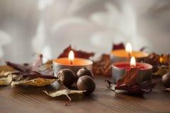 Ξηρά ζωηρόχρωμα φύλλα φθινοπώρου και βελανίδια της βόρειας κόκκινης βαλανιδιάς στον ξύλινο πίνακα με τρία καίγοντας κεριά Στοκ Εικόνες