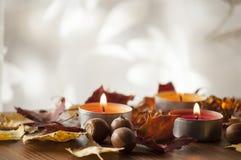 Ξηρά ζωηρόχρωμα φύλλα φθινοπώρου και βελανίδια της βόρειας κόκκινης βαλανιδιάς στον ξύλινο πίνακα με τρία καίγοντας κεριά Στοκ Εικόνα