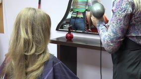 Ξηρά θηλυκή τρίχα κοριτσιών πελατών χτυπήματος στιλίστων κομμωτών στο σαλόνι ομορφιάς 4K απόθεμα βίντεο