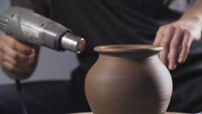 Ξηρά κανάτα αργίλου αγγειοπλαστών με το στεγνωτήρα Χέρια ατόμων που κατασκευάζουν την κανάτα αργίλου r Τέχνη απόθεμα βίντεο