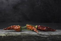 Ξηρά πιπέρια τσίλι στο ξύλο ενάντια σε ένα σκοτεινό έδαφος Στοκ Εικόνα