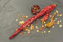Ξηρά πιπέρια τσίλι στη σκοτεινή πλάκα Ισχυρά καρυκεύματα για τα πικάντικα τρόφιμα Διακοσμήστε την κουζίνα στοκ εικόνες