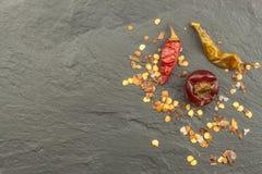 Ξηρά πιπέρια τσίλι στη σκοτεινή πλάκα Ισχυρά καρυκεύματα για τα πικάντικα τρόφιμα Διακοσμήστε την κουζίνα στοκ φωτογραφία