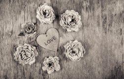 Ξηρά τριαντάφυλλα και μια ξύλινη καρδιά Νεκρά λουλούδια και αγάπη Ρομαντική έννοια μονοχρωματικός Στοκ εικόνες με δικαίωμα ελεύθερης χρήσης