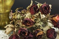Ξηρά τριαντάφυλλα με το βάζο στο σκοτεινό υπόβαθρο Στοκ εικόνα με δικαίωμα ελεύθερης χρήσης