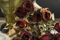 Ξηρά τριαντάφυλλα με το βάζο στο σκοτεινό υπόβαθρο Στοκ Φωτογραφίες