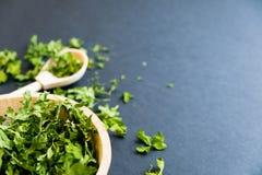 Ξηρά φύλλα cilantro σε ένα ξύλινο κουτάλι Φυσικό φως Εκλεκτική εστίαση Κλείστε επάνω σε ένα μαύρο υπόβαθρο Τοπ άποψη, επίπεδη Στοκ Φωτογραφίες