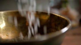 Ξηρά basmati πτώση ρυζιού στο ξύλινο χρυσό κύπελλο μετάλλων στον πίνακα από τη σε αργή κίνηση στενή επάνω μακρο κινηματογράφηση σ φιλμ μικρού μήκους