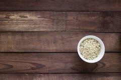 Ξηρές βρώμες σε ένα άσπρο κύπελλο με το κουτάλι σε έναν ξύλινο πίνακα στοκ φωτογραφία με δικαίωμα ελεύθερης χρήσης