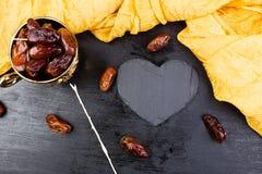 Ξηρές ημερομηνίες φρούτων στο χρυσό φλυτζάνι κοντά στη μαύρη καρδιά πλακών διάστημα αντιγράφων διάνυσμα βαλεντίνων αγάπης απεικόν Στοκ εικόνες με δικαίωμα ελεύθερης χρήσης