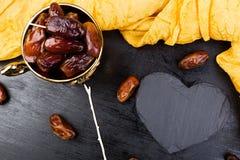 Ξηρές ημερομηνίες φρούτων στο χρυσό φλυτζάνι κοντά στη μαύρη καρδιά πλακών διάστημα αντιγράφων διάνυσμα βαλεντίνων αγάπης απεικόν Στοκ φωτογραφία με δικαίωμα ελεύθερης χρήσης