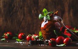 Ξηρές ντομάτες στο ελαιόλαδο με τον πράσινο βασιλικό και καρυκεύματα στο βάζο γυαλιού στον ξύλινο πίνακα κουζινών, αγροτικό ύφος, στοκ εικόνα με δικαίωμα ελεύθερης χρήσης